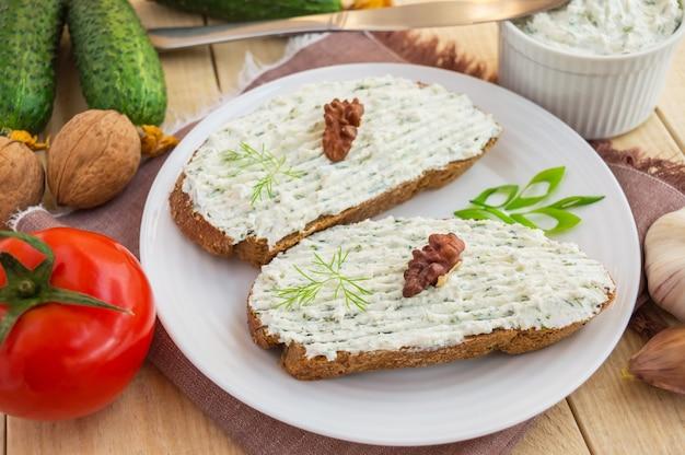 Sandwich nutritif avec pâte de fromage cottage sur pain de seigle sur une plaque blanche.
