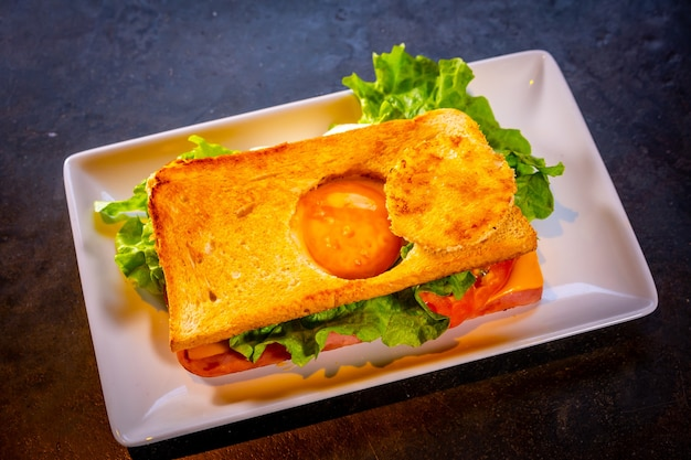 Sandwich avec oeuf au plat et jambon sucré sur fond noir, sur une plaque blanche