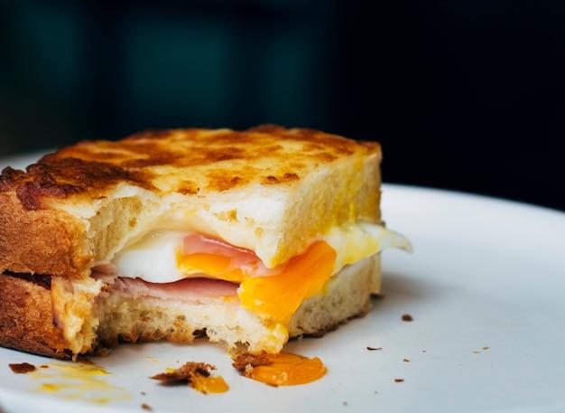 Sandwich oeuf mordu sur une assiette
