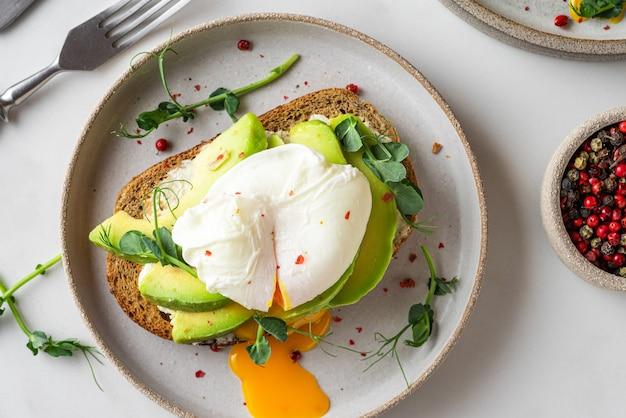 Sandwich avec œuf poché, avocat, pousses et fromage pour un petit-déjeuner sain sur blanc