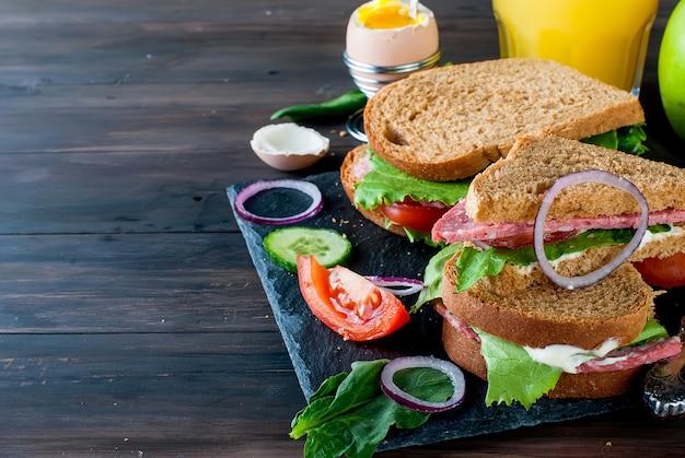 Sandwich, oeuf, tasse de café et verre de jus au petit déjeuner