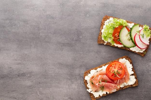 Sandwich avec pain de céréales et salami sur fond de marbre foncé
