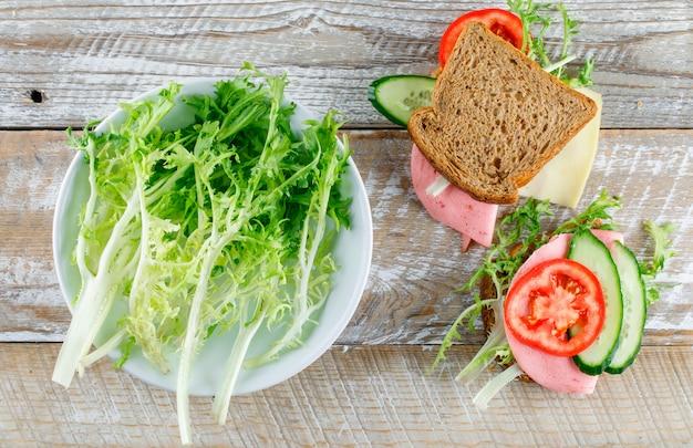Sandwich avec pain, fromage, tomate, concombre, saucisse, verts à plat posé sur une table en bois