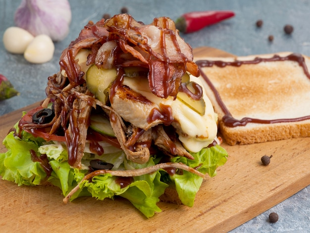 Sandwich ou pain grillé avec bacon de boeuf au poulet et sauce barbecue