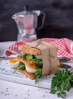 Sandwich de pain grillé et de feuilles de laitue et œuf à la coque, une nourriture végétarienne enveloppée de papier sur une planche de bois blanche