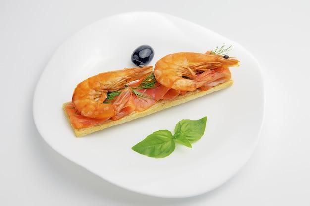 Sandwich ou pain grillé avec des tranches de poisson truite rouge et crevettes avec brin d'aneth en plaque blanche sur fond blanc, alimentation diététique pour la remise en forme
