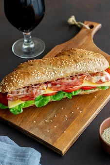 Un sandwich de pain noir avec salade, bacon, tomates et fromage. petit-déjeuner. fast food.