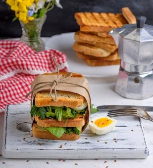 Sandwich de pain perdu, feuilles de laitue et œuf à la coque
