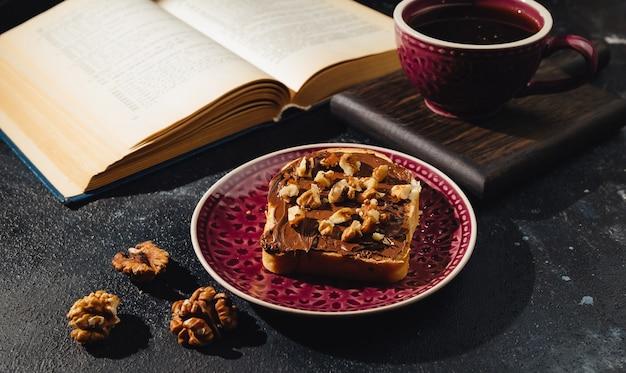 Un sandwich à la pâte de chocolat une tasse de café et un livre ouvert sur fond sombre