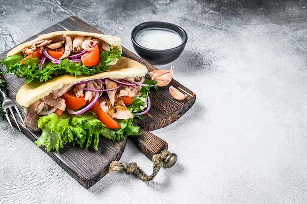 Sandwich pita avec poulet rôti, légumes et sauce délicieuse.
