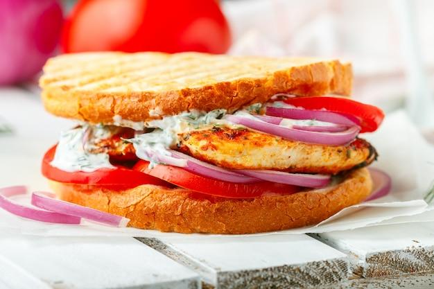 Sandwich avec poitrine de poulet frit, tomates, oignons rouges et sauce tzatziki, apéritif gastronomique