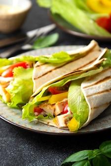 Sandwich roulé au poulet avec légumes frais. délicieux aliments sains sur fond sombre
