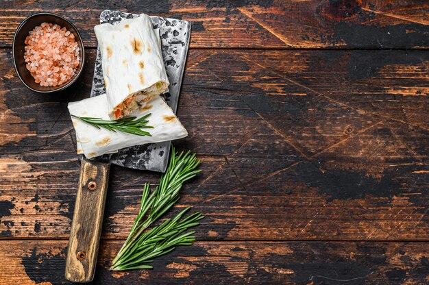 Sandwich roulé au shawarma dans un lavash avec poulet, boeuf, champignons, fromage. fond en bois foncé. vue de dessus. copiez l'espace.