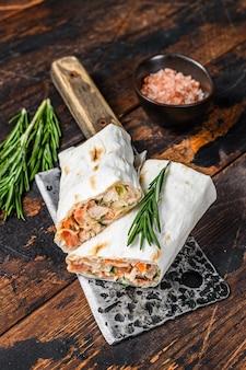 Sandwich roulé au shawarma dans un lavash avec poulet, boeuf, champignons, fromage.