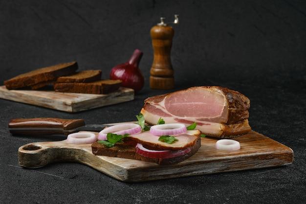 Sandwich rural au bacon fumé avec du pain brun sur une planche à découper en bois