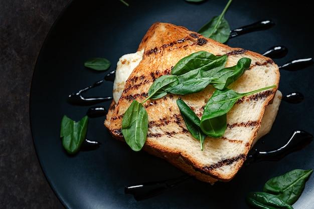 Sandwich sain aux grains entiers, pain grillé croustillant avec des feuilles d'épinards vertes fraîches, avocat, œuf frit et vinaigrette savoureuse. contexte alimentaire. idée, recette pour petit déjeuner ou déjeuner rapide