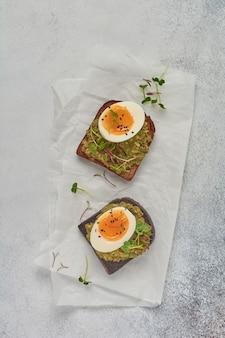 Sandwich sain avec avocat, œufs et micropousses sur du pain grillé sur une assiette de service pour le petit déjeuner. concept diététique de nutrition saine. vue de dessus.