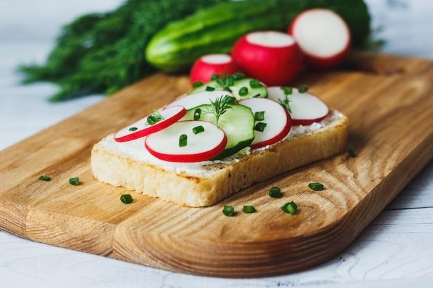 Sandwich sain avec radis concombre et fromage à la crème sur une planche à découper en bois