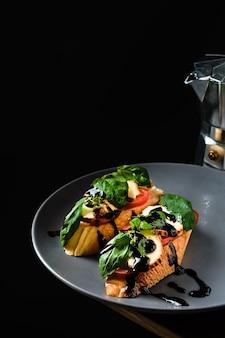 Sandwich santé sur une baguette fraîche avec basilic, tomates, fromage grillé et sauce balsamique. gros plan avec espace copie, idée de petit-déjeuner