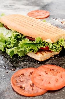 Sandwich avec saucisse, poivre, fromage et salade