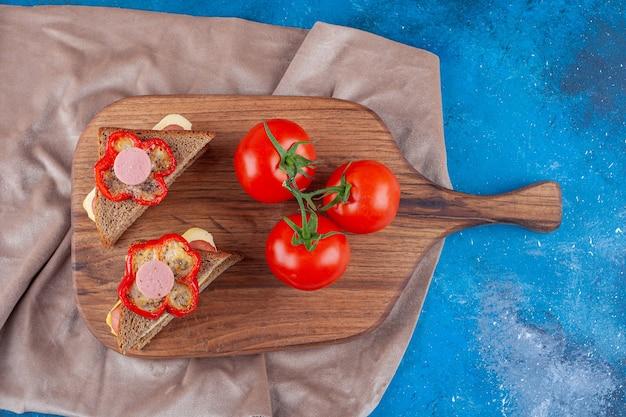 Sandwich avec saucisse et tomates entières sur une planche à découper sur un morceau de tissu, sur le bleu.