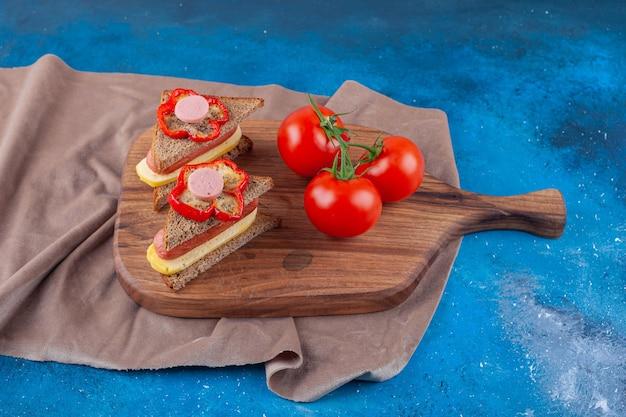 Sandwich avec saucisse et tomates entières sur une planche à découper sur un morceau de tissu, sur la table bleue.