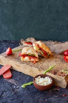 Sandwich à la saucisse turque coupé en morceaux sur une planche de bois