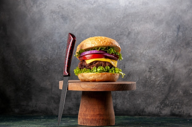 Sandwich savoureux et fourchette rouge sur une planche à découper en bois sur une surface de couleur sombre avec un espace libre