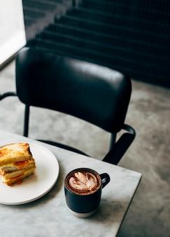 Sandwich et une tasse de café sur une table