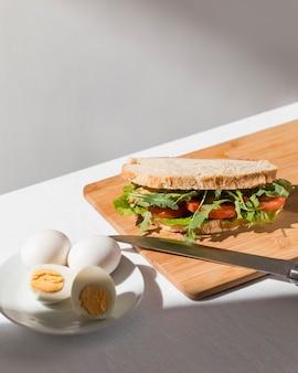 Sandwich toast à angle élevé avec tomates, légumes verts et œufs durs