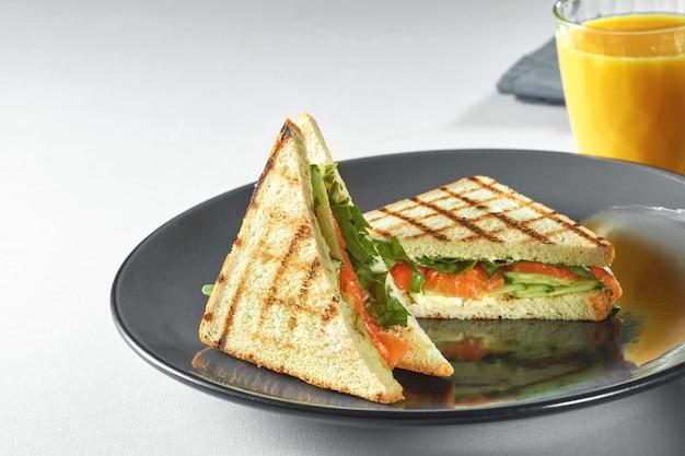 Sandwich toast au saumon, légumes et salade sur assiette et jus d'orange frais