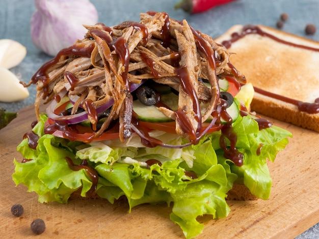 Sandwich ou toast copieux avec porc et sauce barbecue