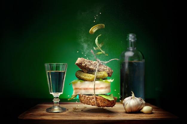Un sandwich avec une tranche de bacon sur fond vert avec des ingrédients volants cornichons et roquette et ail