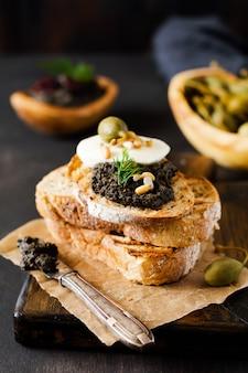 Sandwich avec une tranche de fromage mozzarella et tapenade, câpres sur fond de table rustique foncé