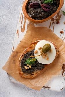 Sandwich avec tranche de mozzarella et tapenade, câpres sur fond de table rustique gris clair. plat traditionnel provençal. mise au point sélective