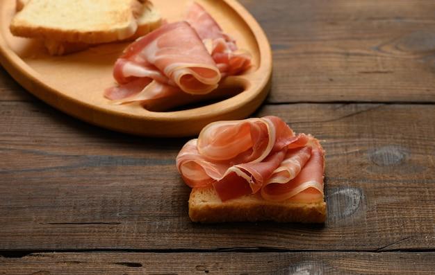 Sandwich avec une tranche de pain carrée blanche et des tranches de prosciutto sur une planche de bois