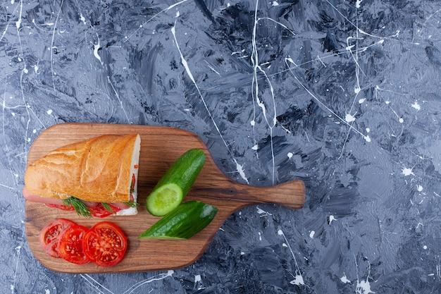 Sandwich, tranches de concombre et tomates sur une planche à découper sur bleu.