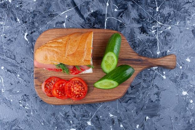 Sandwich, tranches de concombre et tomates sur une planche à découper, sur la table bleue.