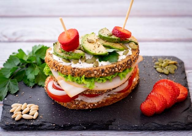 Sandwich à trois couches avec une variété d'ingrédients dans un pain de blé entier avec des graines alimentation saine