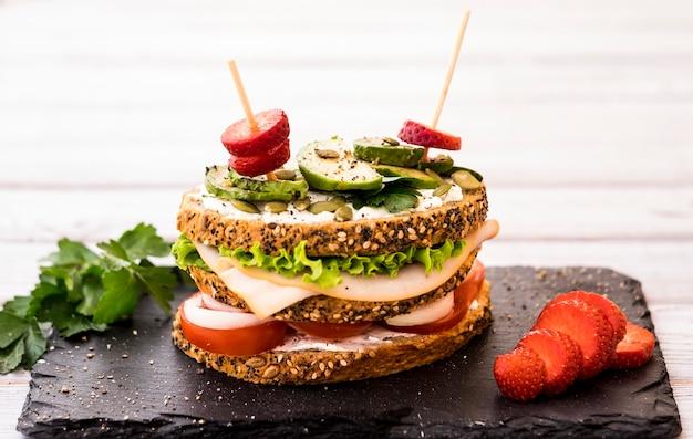 Sandwich à trois couches avec une variété de légumes, de viande de dinde et d'avocat dans un pain de blé entier avec des graines. fraise rouge. concept d'alimentation saine.