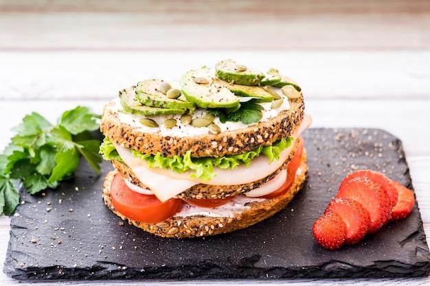 Sandwich à trois couches avec variété de légumes, viande de dinde et avocat dans un pain de blé entier