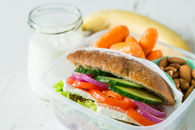 Sandwich végétalien dans une boîte à lunch avec carottes et noix