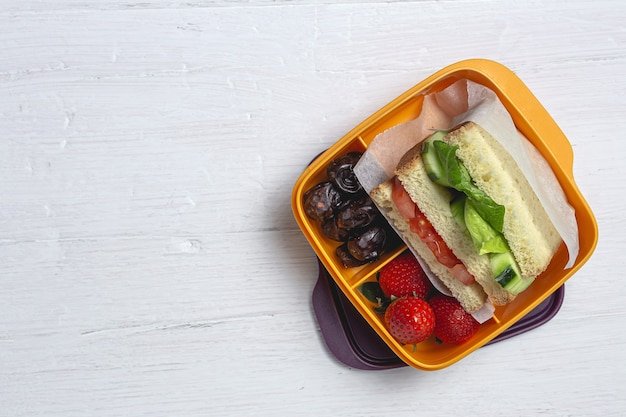 Sandwich végétalien dans un récipient en plastique sur fond de bois. concept d & # 39; alimentation saine