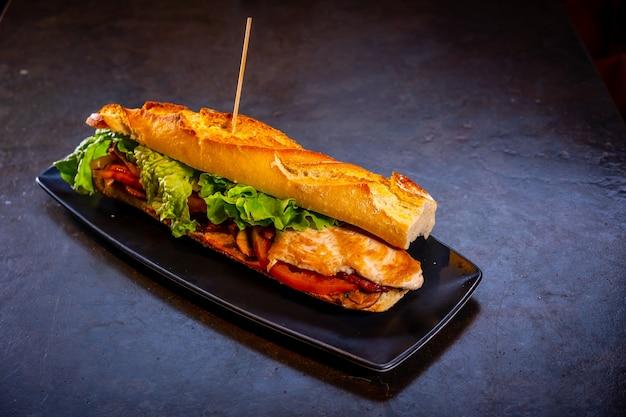 Sandwich végétarien au poulet sur fond noir, sur une plaque blanche