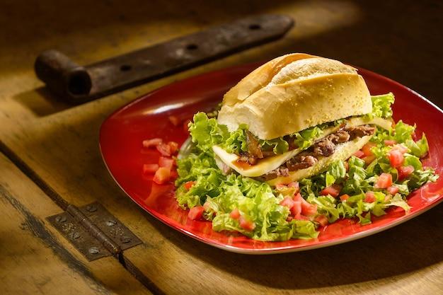 Sandwich à la viande et au fromage, avec laitue et tomate, sur une table en bois et avec un éclairage contrasté.