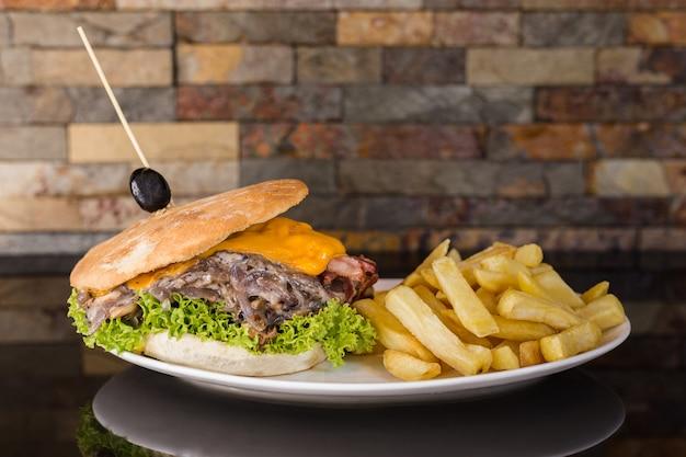 Sandwich à la viande avec du fromage cheddar, des champignons, de l'oignon, de la laitue, des tomates, du bacon et des frites