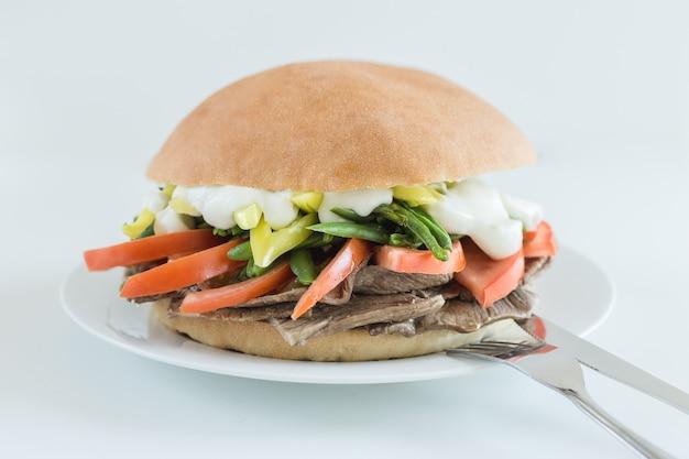 Sandwich à la viande avec tomates, haricots verts, chili et mayonnaise sur fond blanc
