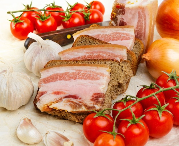 Des sandwiches au bacon salé sur du pain de seigle. avec tomates cerises et ail.