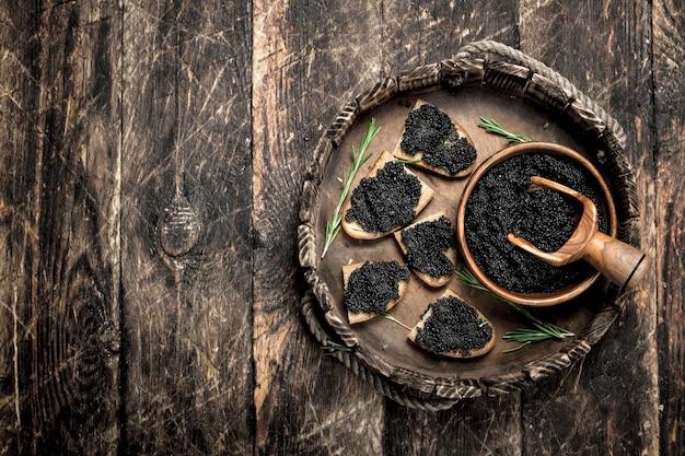 Sandwiches au caviar noir sur vieux plateau sur table en bois.