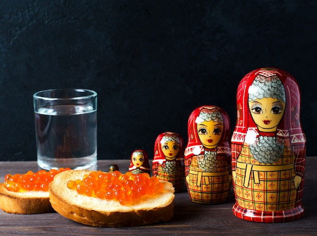 Sandwiches au caviar rouge de poisson saumon. un verre de vodka, matryoshka.